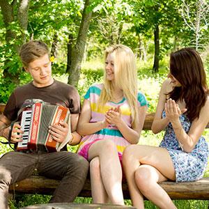 dečko svira harmoniku djevojkama