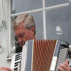 stariji čovijek svira harmoniku